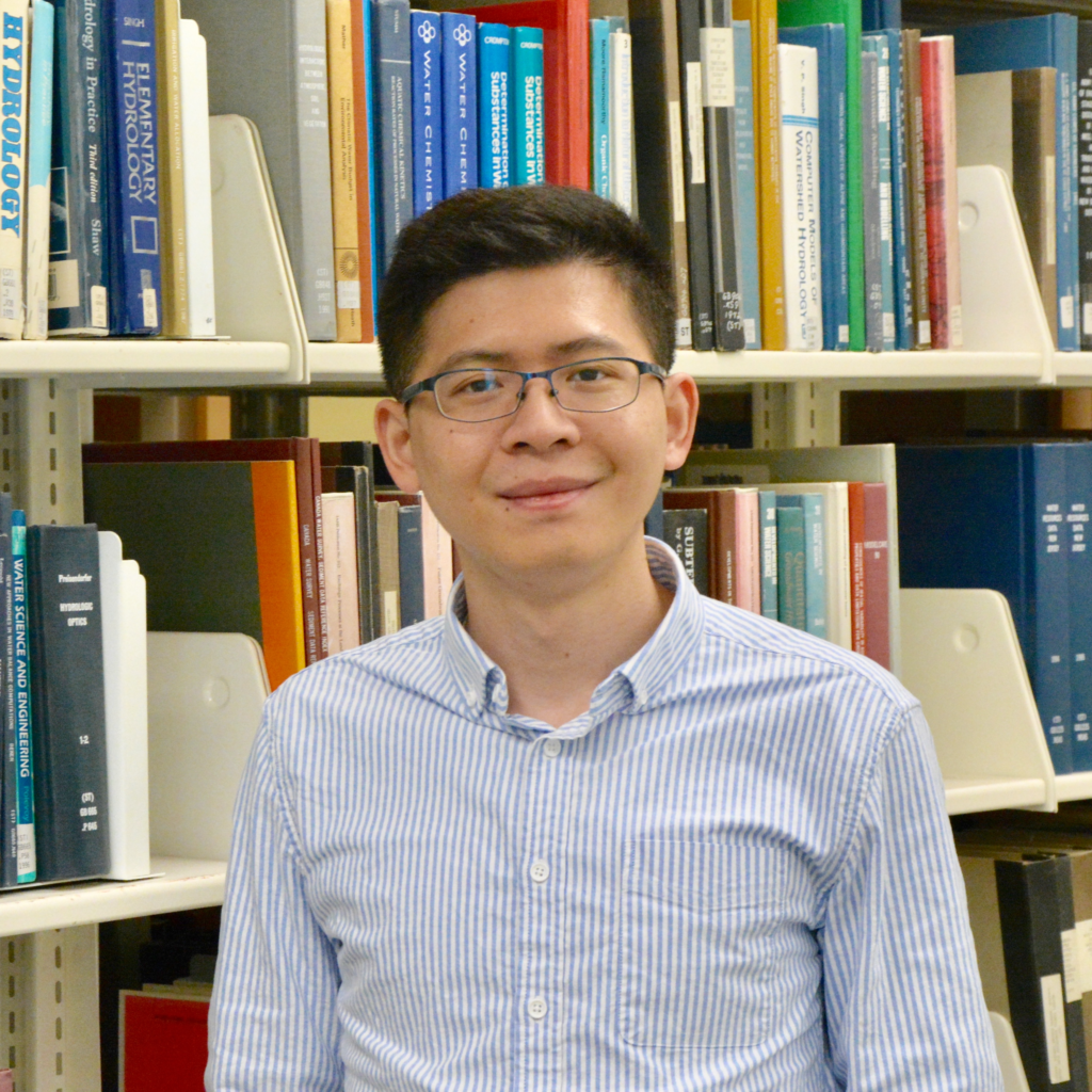 Photo of Jie Feng in front of bookshelf