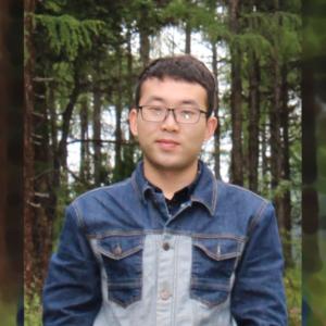 Bingqiang Ji standing in a forest